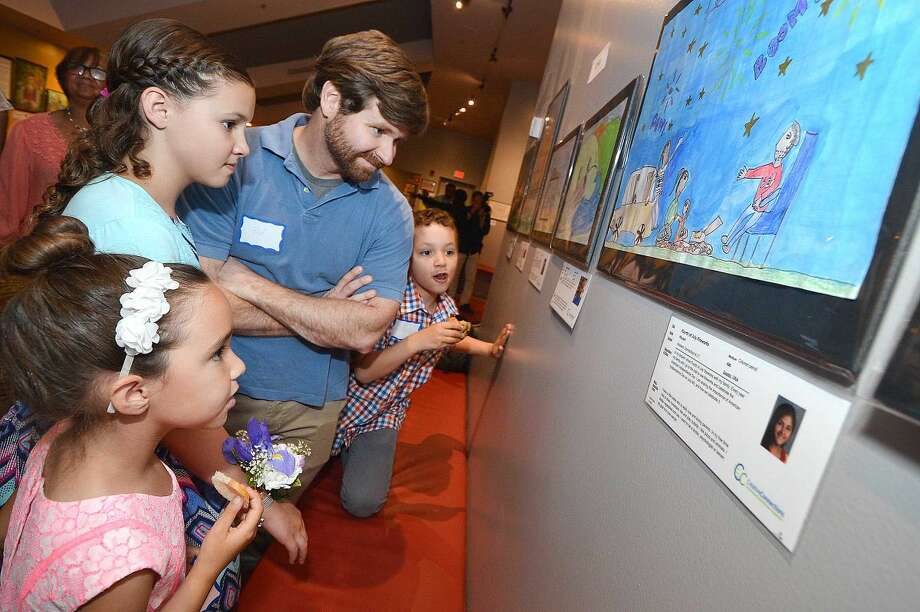 """Hour Photo/Alex von Kleydorff Quinn McGeary from North Mianus School in Greenwich finds her pianting, """" Catskill Summer"""" with dad Edward, sister Kai and brother Kaes during the reception for the 2015 International Childrens Art Exhibit at The Maritime Aquarium"""