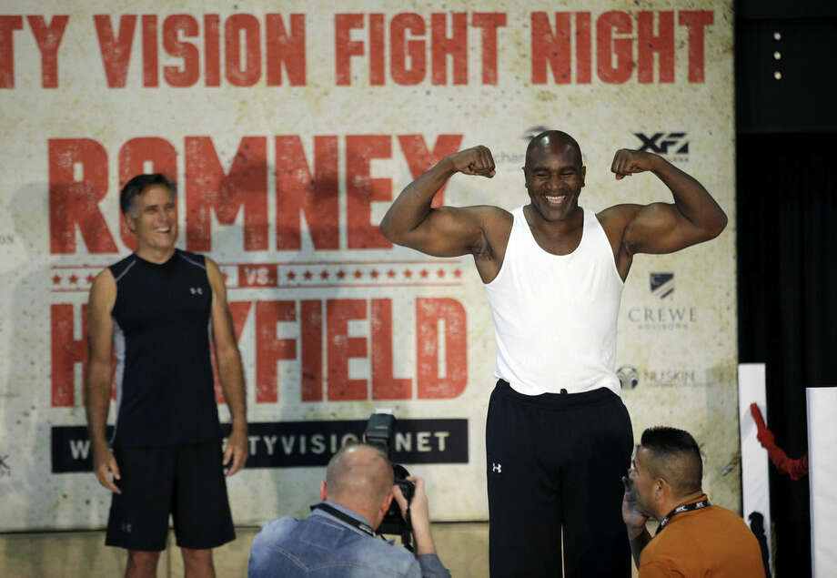 Former Republican presidential candidate Mitt Romney, left, looks on as five-time heavyweight boxing champion Evander Holyfield weighs-in Thursday, May 14, 2015, in Holladay, Utah. Romney and Holyfield are set to square off at a charity fight on Friday, May 15, in Salt Lake City. The black-tie event will raise money for the Utah-based organization CharityVision, which helps doctors in developing countries perform surgeries to restore vision in people with curable blindness. (AP Photo/Rick Bowmer)