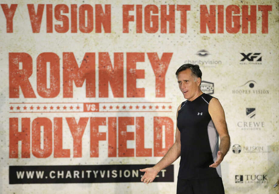 Former Republican presidential candidate Mitt Romney talks during an official weigh-in with five-time heavyweight boxing champion Evander Holyfield, Thursday, May 14, 2015, in Holladay, Utah. Romney and Holyfield are set to square off at a charity fight on Friday, May 15, in Salt Lake City. The black-tie event will raise money for the Utah-based organization CharityVision, which helps doctors in developing countries perform surgeries to restore vision in people with curable blindness. (AP Photo/Rick Bowmer)