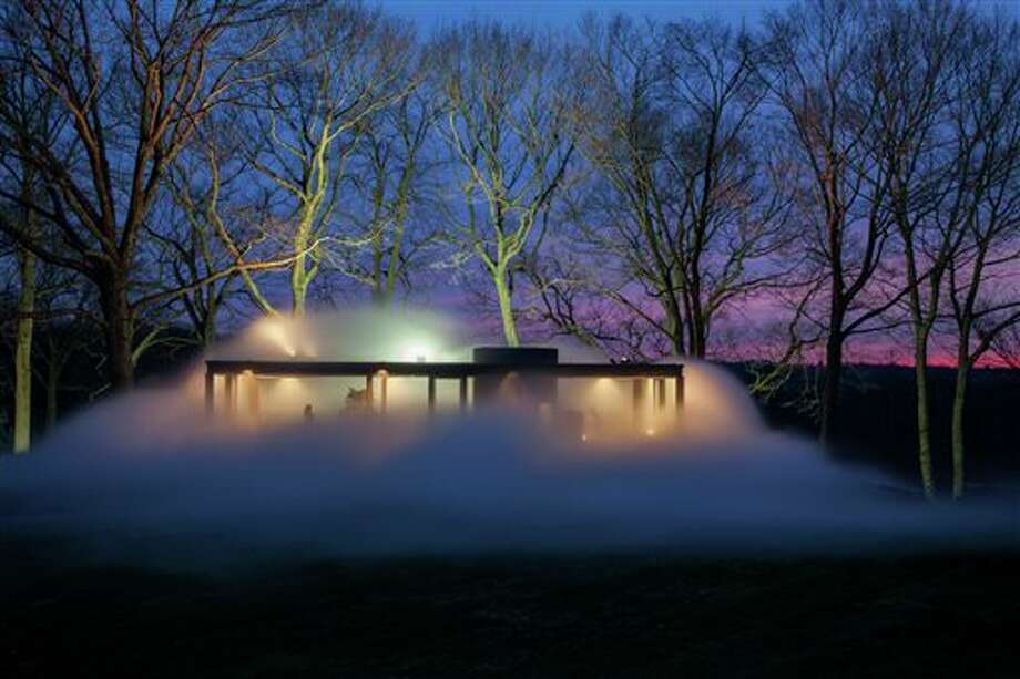 """This Friday, April 18, 2014 photo provided by courtesy of The Glass House shows a """"sculpture"""" of dense fog moving in the wind, created by Tokyo-based artist Fujiko Nakaya, using 600 carefully calibrated nozzles, surrounding Philip Johnson's iconic 1949 Glass House. Like the glass structure itself, """"Fujiko Nakaya: Veil"""" plays on the visible and invisible, transparent and opaque, permanent and ephemeral. The installation, about an hour's train ride north of New York City, is open to the public from May 1 to November 30, 2014. / Courtesy The Glass House"""