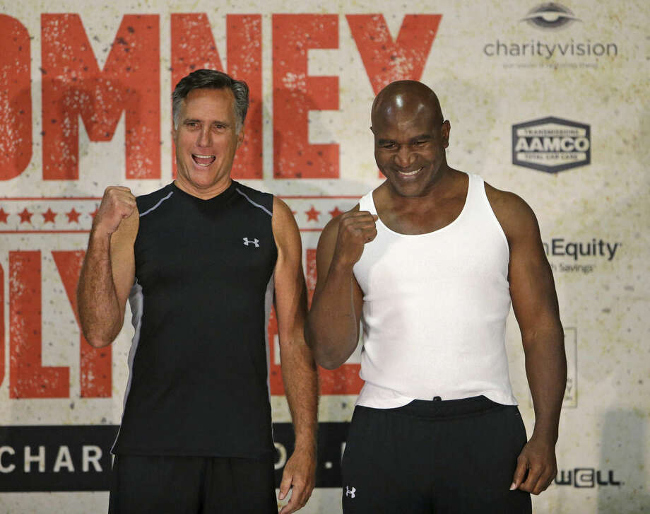 Former Republican presidential candidate Mitt Romney, left, and five-time heavyweight boxing champion Evander Holyfield pose for a photo after an official weigh-in Thursday, May 14, 2015, in Holladay, Utah. Romney and Holyfield are set to square off at a charity fight on Friday, May 15, in Salt Lake City. The black-tie event will raise money for the Utah-based organization CharityVision, which helps doctors in developing countries perform surgeries to restore vision in people with curable blindness. (AP Photo/Rick Bowmer)