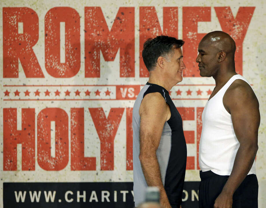 Former Republican presidential candidate Mitt Romney, left, and five-time heavyweight boxing champion Evander Holyfield face each other during an official weigh-in Thursday, May 14, 2015, in Holladay, Utah. Romney and Holyfield are set to square off at a charity fight on Friday, May 15, in Salt Lake City. The black-tie event will raise money for the Utah-based organization CharityVision, which helps doctors in developing countries perform surgeries to restore vision in people with curable blindness. (AP Photo/Rick Bowmer)