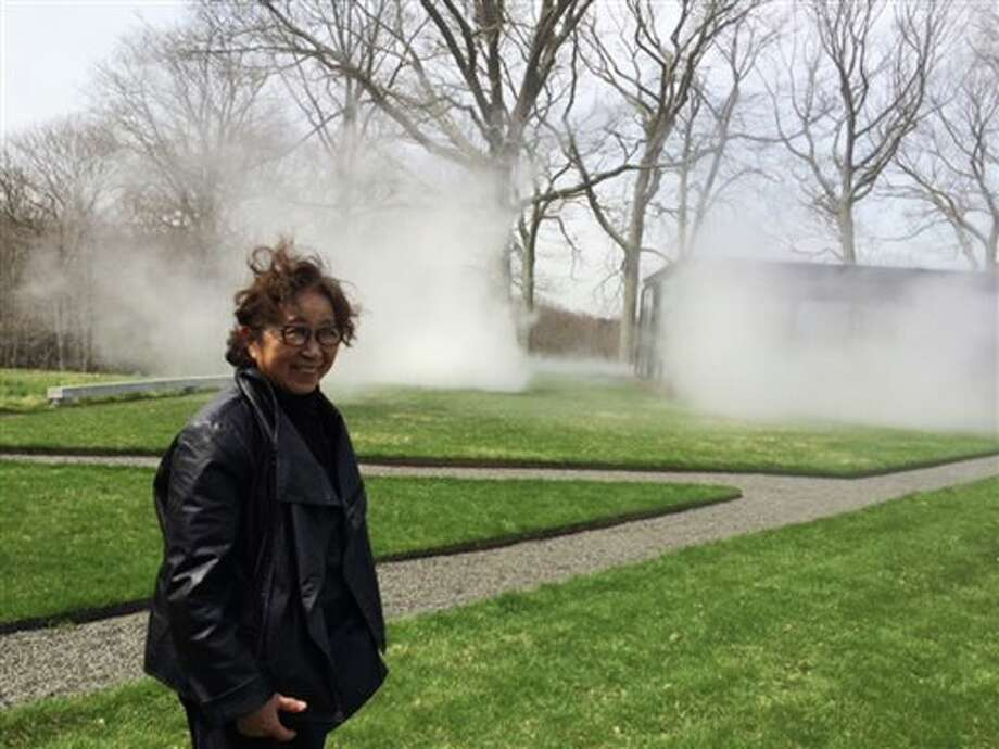 """This April 22, 2014 photo shows Japanese artist, Fujiko Nakaya, internationally known for her """"fog sculptures,"""" on the site of her new fog installation at the Glass House, in New Canaan, Conn. Nakaya has just installed a work in which 600 carefully-calibrated nozzles periodically exude fog around Philip Johnson's iconic architecture, which can be viewed from inside or outside the Modernist glass structure. It is her first installation on the east coast in 30 years and is meant to make invisible forces like wind more apparent, while concealing the usually visible. / AP"""