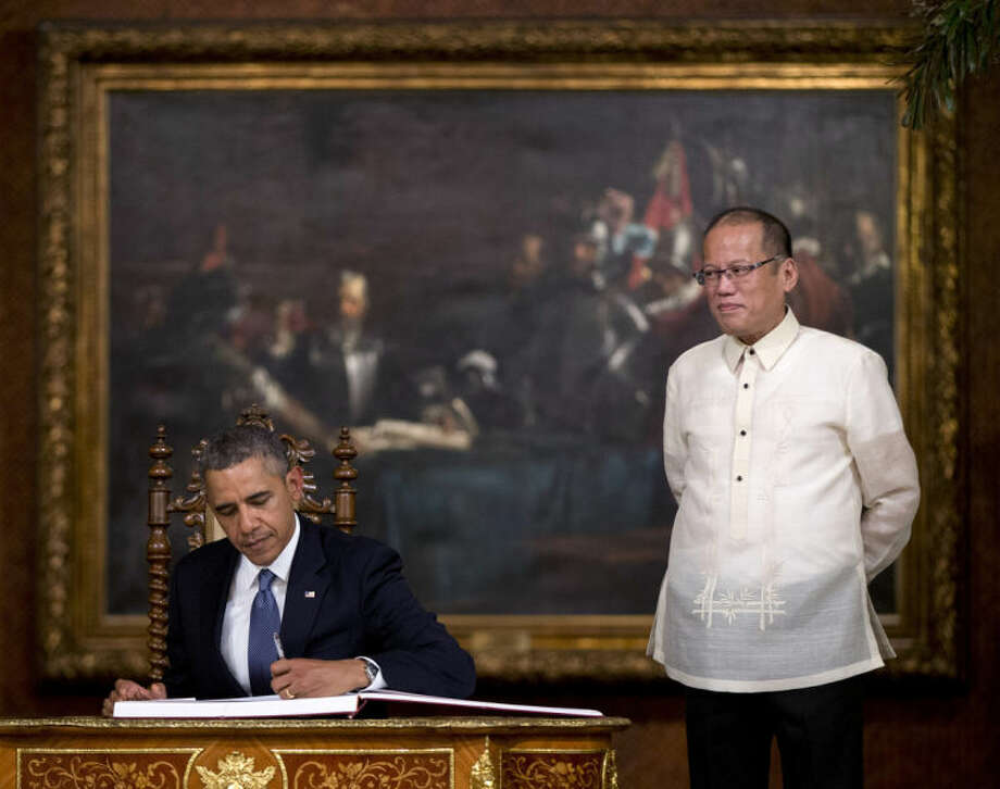 FILE - In this Monday, April 28, 2014 file photo, U.S. President Barack Obama signs a guestbook as Philippine President Benigno Aquino III looks on at the Malacanang Palace in Manila. A new defense pact that will allow thousands of U.S. troops to be temporarily based in Philippines for the first time in more than 20 years signals closer cooperation in the allies' hot-and-cold relationship that has been shaped over the decades by war, terrorism and now, jitters over China's rise. The 10-year agreement, signed Monday as Obama arrived in Manila, was considered the centerpiece of his four-nation Asian trip, which he used to reassure allies like Japan and the Philippines of American military backing as they wrangle with China in increasingly tense territorial disputes. (AP Photo/Carolyn Kaster, File)