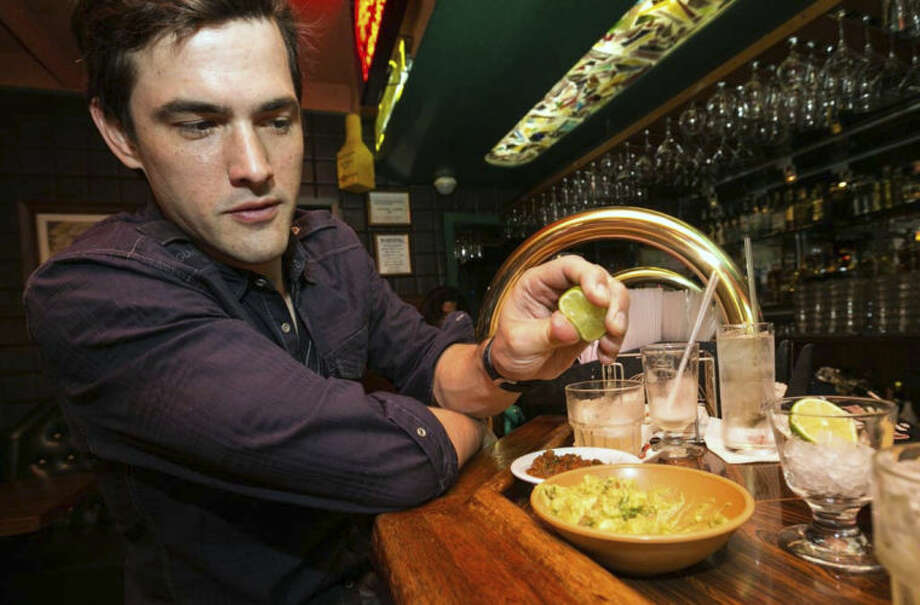 "In this Monday, April 28, 2014 photo, Dana Stolzner squeezes lime juice to his guacamole, while drinking his own ""Dana Margarita"" a coconut based margarita cocktail at the bar of El Coyote, a Mexican restaurant in Los Angeles. Thousands of restaurateurs from coast to coast who have fallen victim to the Great Green Citrus Crisis of 2014. The price of a lime has skyrocketed in recent weeks, quadrupling or, in some areas, going even higher. (AP Photo)"