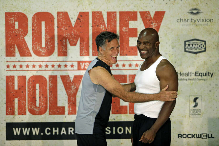 Former Republican presidential candidate Mitt Romney, left, and five-time heavyweight boxing champion Evander Holyfield laugh during an official weigh-in Thursday, May 14, 2015, in Holladay, Utah. Romney and Holyfield are set to square off at a charity fight on Friday, May 15, in Salt Lake City. The black-tie event will raise money for the Utah-based organization CharityVision, which helps doctors in developing countries perform surgeries to restore vision in people with curable blindness. (AP Photo/Rick Bowmer)