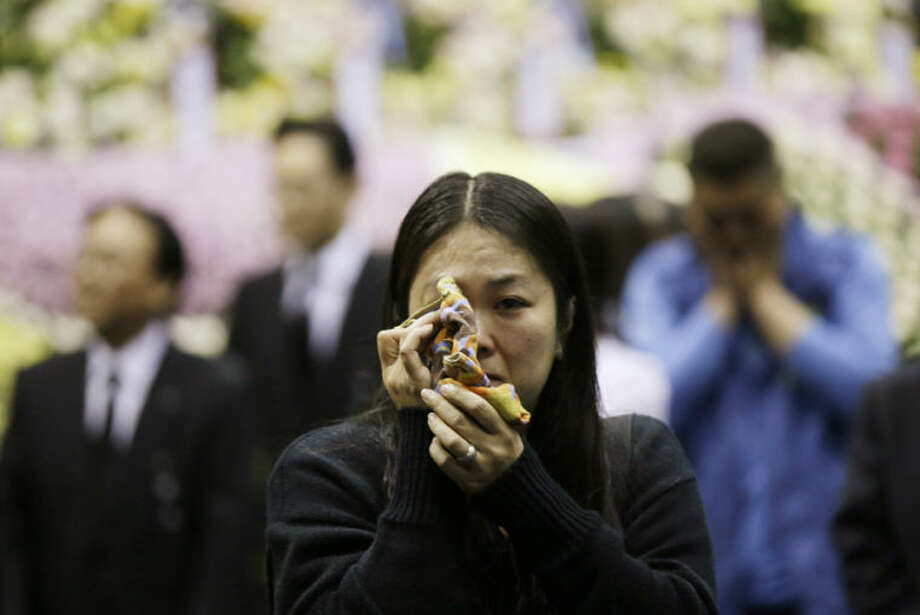 Lee Won-a, 40, wipes her tears after paying tribute to the victims of the sunken ferry Sewol, at a memorial altar in Ansan, south of Seoul, South Korea, Wednesday, April 30, 2014. Two weeks after the ferry sank off South Korea's southern cost, divers have recovered scores of bodies from the wreckage, but they fought strong currents and floating debris inside the ship Wednesday as they searched for the rest still missing. (AP Photo/Lee Jin-man)