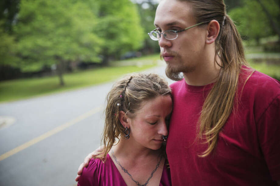 Anthony Ward, 20, right, holds his girlfriend Rachel Hope Boggs, 24, as they recount their run-in with a gunman who opened fire Tuesday in a FedEx package-sorting center where they worked, Wednesday, April 30, 2014, in Kennesaw, Ga. Police said 19-year-old Geddy Kramer shot a guard at the facility on Tuesday, then opened fire at others inside the warehouse. Investigators said Kramer killed himself, which stopped the rampage. (AP Photo/David Goldman)