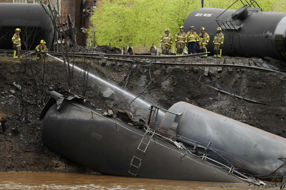 Firefighters and rescue workers work along the tracks where several CSX tanker cars carrying crude oil derailed and caught fire along the James River near downtown in Lynchburg, Va., Wednesday, April 30, 2014. Police said that more than a dozen tanker cars were involved in the derailment.(AP Photo/Steve Helber)