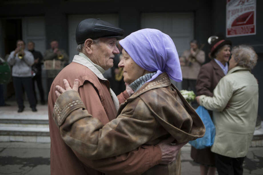 An elderly couple dances as local citizens gather to mark May Day in Slovyansk, eastern Ukraine, Thursday, May 1, 2014. Russian state news media were quick to dismiss the protests as the work of Ukrainian neo-Nazis, a particularly loaded accusation because Ukrainian nationalists collaborating with the Nazis are blamed for horrific reprisal attacks during World War II. (AP Photo/Alexander Zemlianichenko)