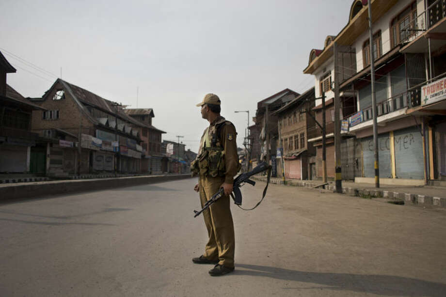 An Indian paramilitary soldier stands in the middle of an empty street during a shutdown following calls by rebels and separatist politicians to boycott the Indian parliamentary elections in Srinagar, India, Wednesday, April 30, 2014. Authorities detained more than 600 Kashmiri residents in a crackdown on suspected separatists ahead of Wednesday's voting, police said Tuesday. Indian Kashmir elects only six members of India's 543-seat Parliament. Voting is being held over several days in the restive region so security forces can better guard the polls.(AP Photo/Bernat Armangue)