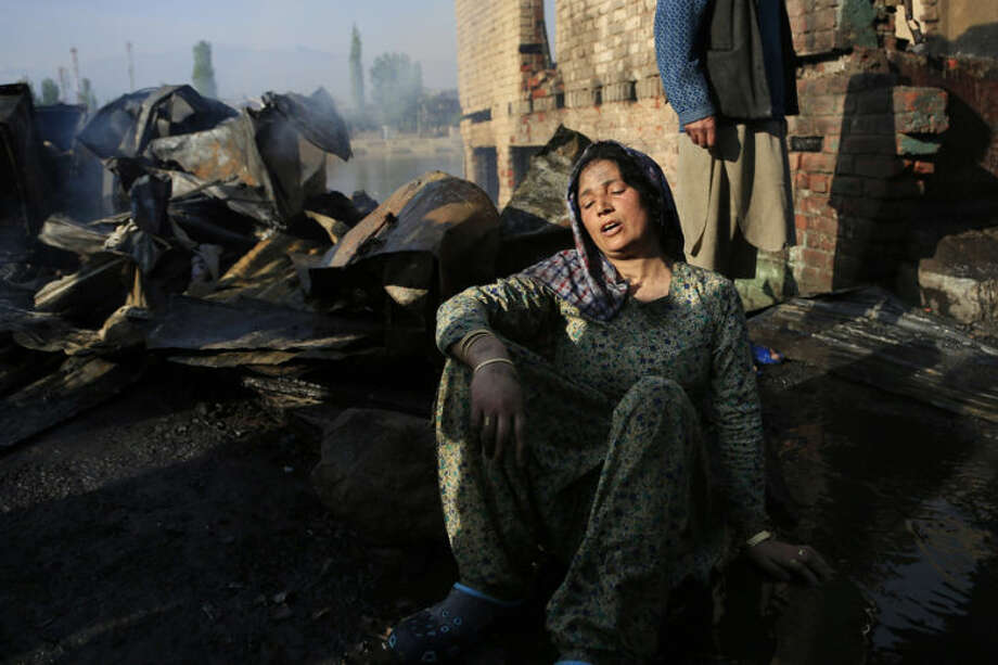 A Kashmiri woman wails after a fire destroyed a shanty that was her home in Srinagar, India, Tuesday, April 29, 2014. According to officials at least twenty seven shanties and two multi story buildings were gutted in Tuesday's fire, the cause of which is not known. No casualties have been reported so far. (AP Photo/Dar Yasin)