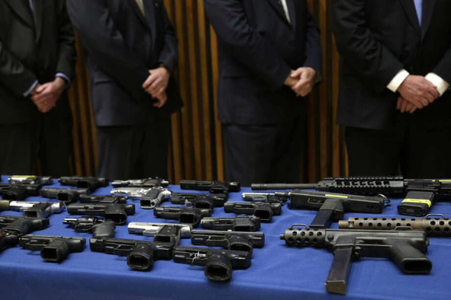 Police officers stand next to a table of guns on display during a news conference at police headquarters in New York, Wednesday, April 30, 2014. Authorities in New York City say they've arrested six people and charged them with selling 155 guns transported from Georgia to an undercover officer in Brooklyn. (AP Photo/Seth Wenig)