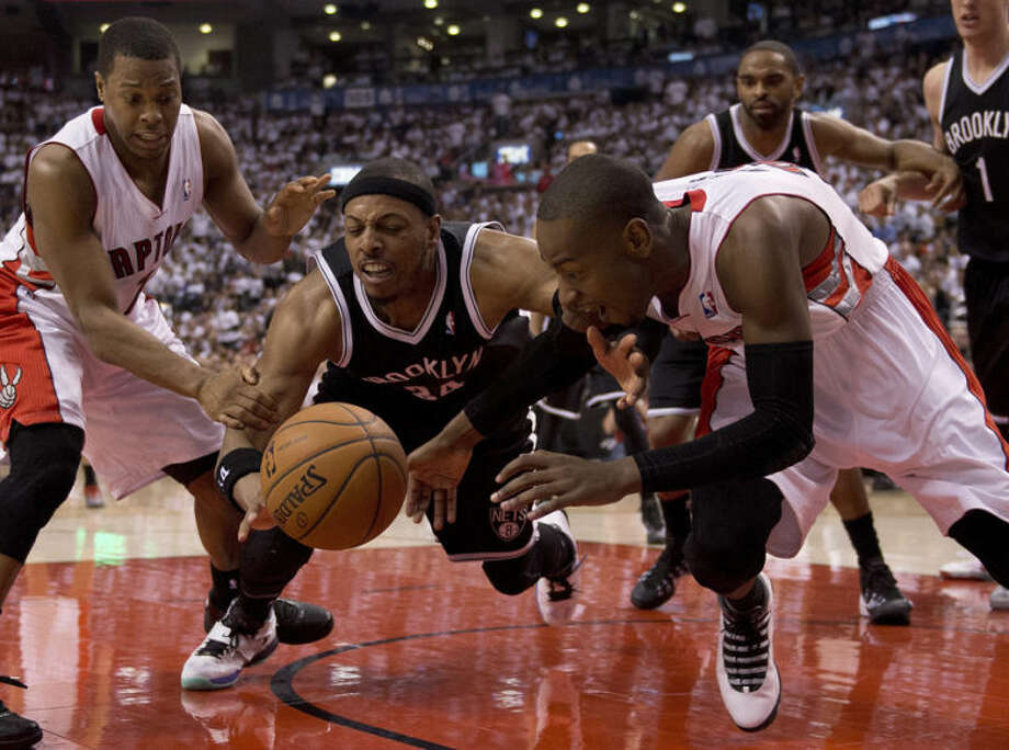 Toronto Raptors guard Kyle Lowry, left, and Terrence Ross, right, battle for a loose ball with Brooklyn Nets forward Paul Pierce during the first half of Game 5 of the opening-round NBA basketball playoff series in Toronto, Wednesday, April 30, 2014. (AP Photo/The Canadian Press, Frank Gunn)