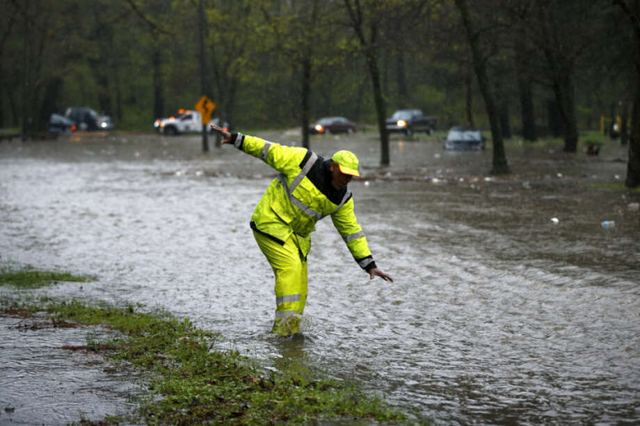 A tow truck worker stumbles as he walks across a flooded section of the Cobbs Creek Parkway, Wednesday, April 30, 2014, in Philadelphia. (AP Photo)