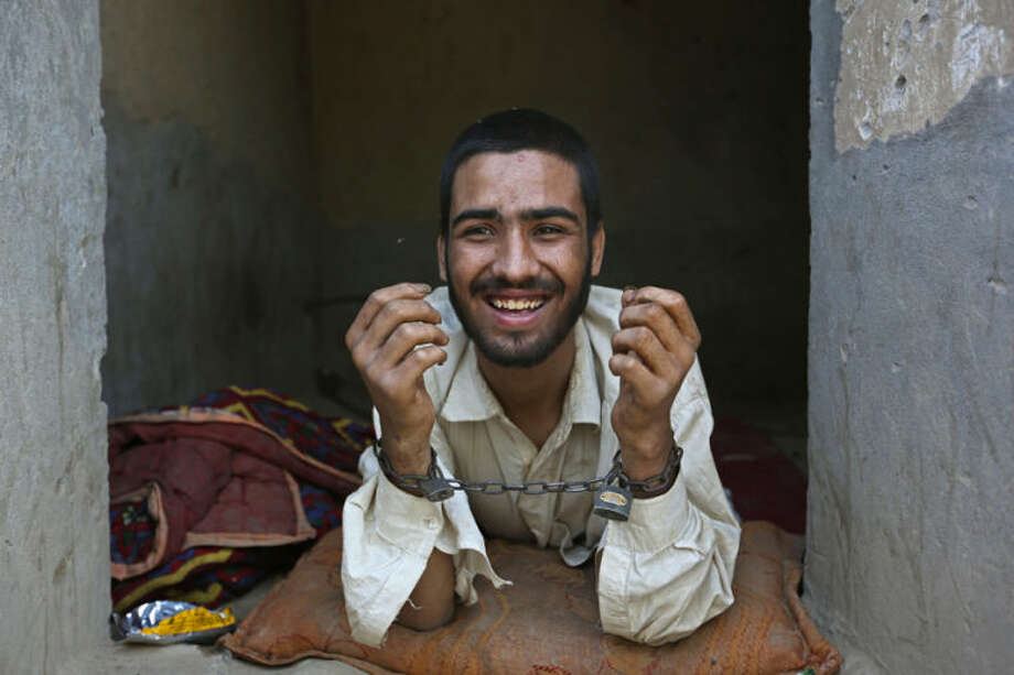 Muhibullah, 20, a drug addict, is handcuffed in a cell in his 40-day incarceration at the Mia Ali Baba shrine in Jalalabad, Afghanistan, Thursday, May 1, 2014. It is believed locally that 40 days of chaining to a wall with a restricted diet at the 300-year old shrine can cure the mentally ill, drug addicts and those possessed by spirits. If a shrine keeper decides their situation is improving, they may be unchained for a few minutes. However, shrines such as Mia Ali Baba are frowned upon by health care professionals and other critics who say the remedy is ineffective and that those who run the incarceration prey on vulnerable people's religious beliefs and superstitions to make a profit. (AP Photo/Rahmat Gul)