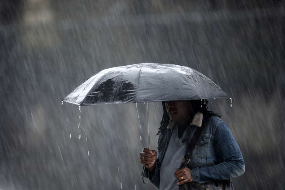 A pedestrian crosses the street in a rainstorm, Wednesday, April 30, 2014, in Philadelphia. The area can expect widespread showers with possible thunderstorms with a flood watch in effect through Thursday morning. (AP Photo)
