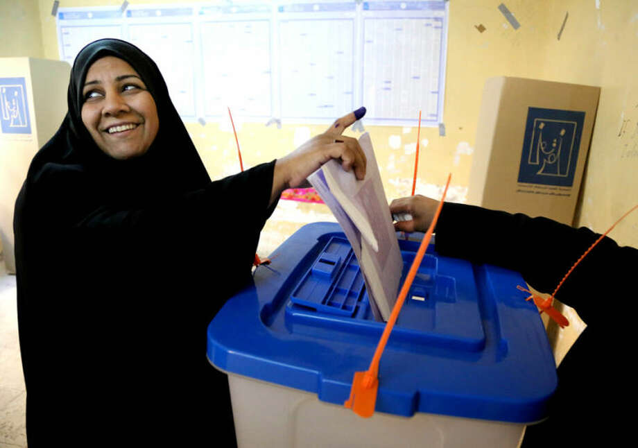 An Iraqi woman casts her vote inside a polling station for parliamentary elections in Baghdad, Iraq, Wednesday, April 30, 2014. Iraq is holding its third parliamentary elections since the U.S.-led invasion that toppled dictator Saddam Hussein. More than 22 million voters are eligible to cast their ballots to choose 328 lawmakers out of more than 9,000 candidates. (AP Photo/Karim Kadim)