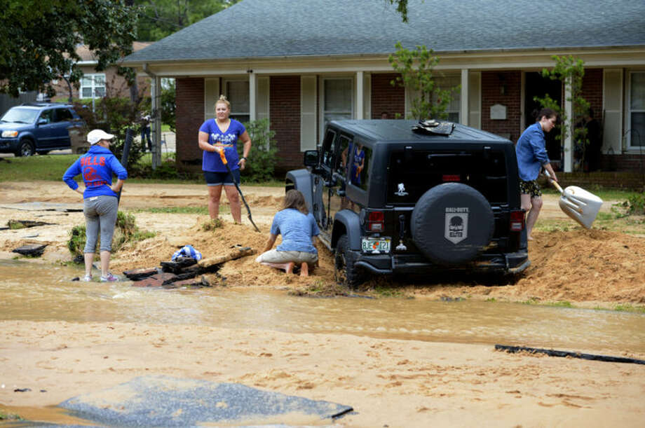 Barbara Erdos, far left, watches as Marguerite Lysek, left, Dr. Zoltan Erdos, kneeling, and Kristen Broussard, right help dig Erdos' stuck Jeep out of axel-deep mud on Piedmont Street after flood-water devastation caused by torrential rains in Pensacola, Fla., Wednesday, April 30, 2014. (AP Photo/G.M. Andrews)