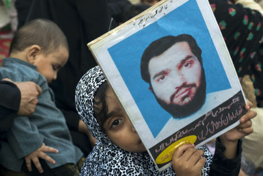 "A Pakistani girl holds a picture of her missing father sitting at a camp in Islamabad, Pakistan, Wednesday, April 30, 2014. Family members and human rights activists held a protest to demand information from the government about missing people who were reportedly picked up by security agencies during anti al-Qaida raids. Writing on a poster reads"" prime minister where is my dad."" (AP Photo/B.K. Bangash)"