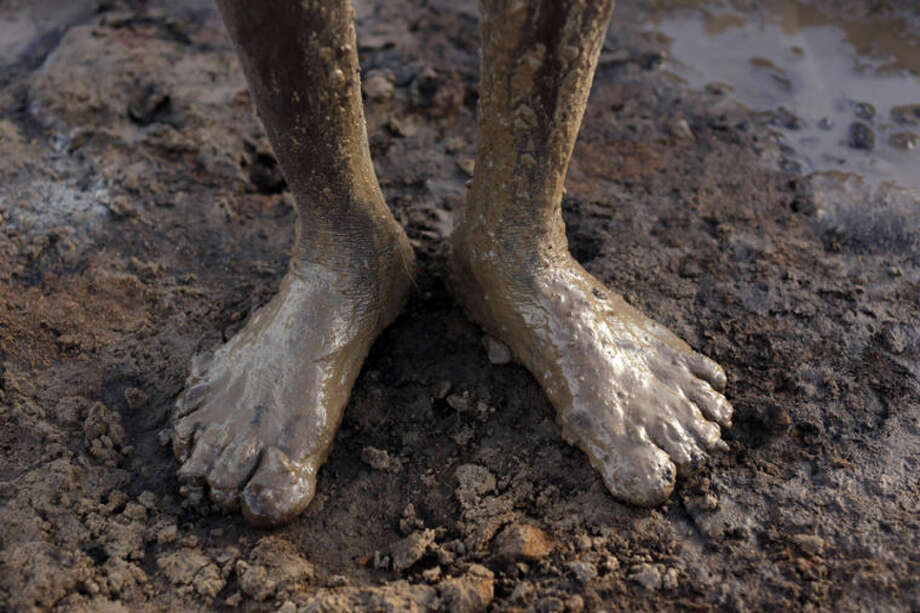 An Indian laborer's legs are covered in mud as he works at a brick- manufacturing unit on the eve of International Labor Day in Chennai, India, Wednesday, April 30, 2014. (AP Photo/Arun Sankar K)
