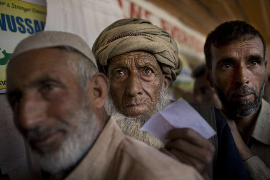 A Kashmiri man belonging to the nomadic Gujjar tribe, center, lines-up to cast his vote during the Indian parliamentary elections at a polling station in Wasun, about 35 kilometers (22 miles) northeast of Srinagar, India, Wednesday, April 30, 2014. Authorities detained more than 600 Kashmiri residents in a crackdown on suspected separatists ahead of Wednesday's voting, police said Tuesday. Indian Kashmir elects only six members of India's 543-seat Parliament. Voting is being held over several days in the restive region so security forces can better guard the polls.(AP Photo/Bernat Armangue)