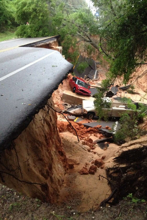 A car lies at the bottom of a ravine after the Scenic Highway collapsed near Pensacola, Fla., Wednesday April 30, 2014. Heavy rains and flooding have left people stranded in houses and cars in the Florida Panhandle and along the Alabama coast. According to the National Weather Service, an estimated 15-20 inches of rain has fallen in Pensacola in the past 24 hours. (AP Photo/Pensacola News Journal, Katie E. King)