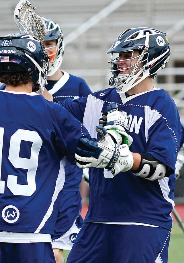 Hour photo / Erik Trautmann Brien McMahon High School lacrosse battles Wilton High School Saturday at Cassagrande Field.