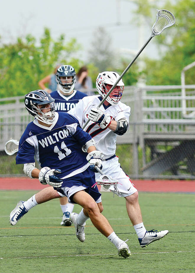 Hour photo / Erik Trautmann Brien McMahon High School lacrosse battles Wilton High School Saturday at Cassagrande Field.