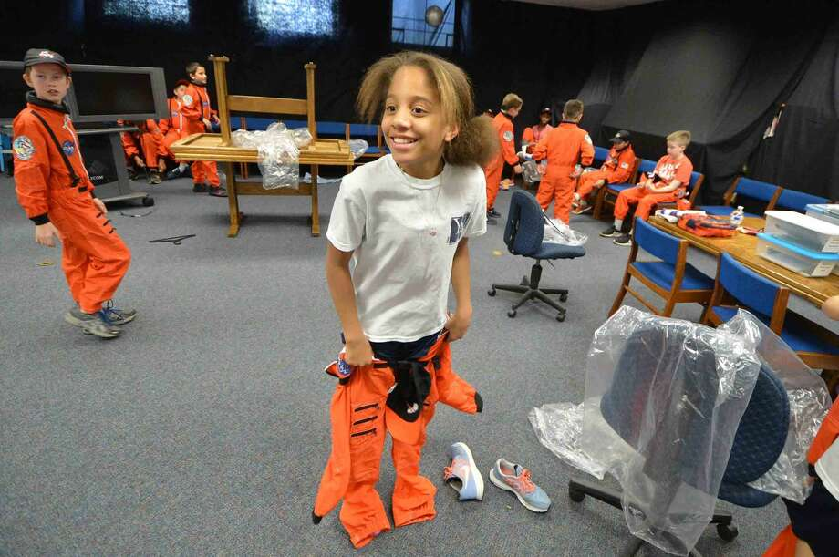 Lena Johnson jumps to get into her flight suit for Columbus Magnet School Young Astronauts launch of a dozen rockets to commemorate the Space Shuttle Challenger and its crew