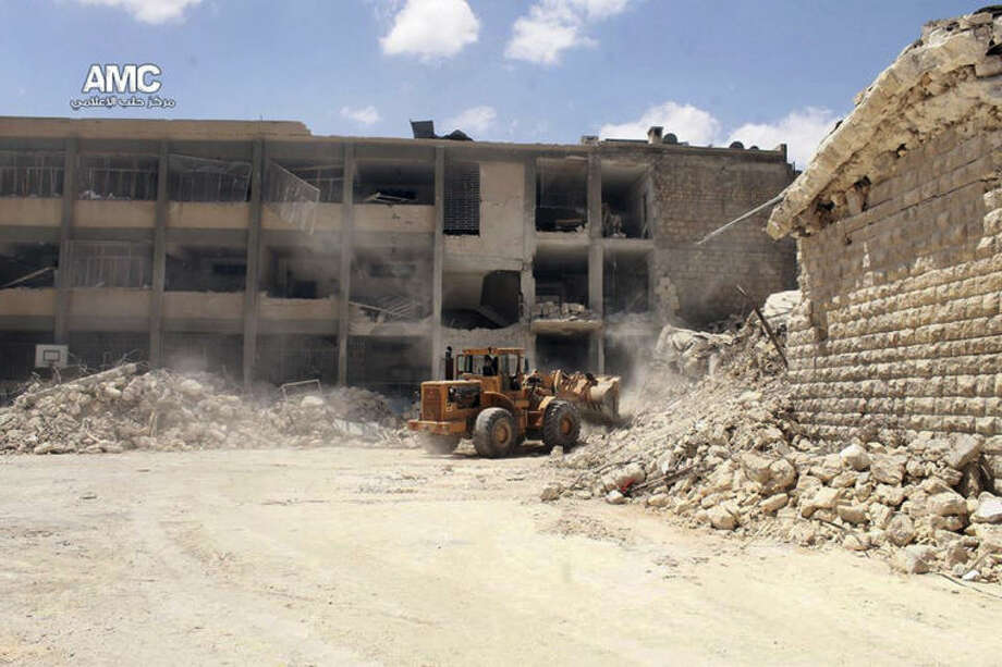 This photo provided by the anti-government activist group Aleppo Media Center (AMC), which has been authenticated based on its contents and other AP reporting, shows a bulldozer removing the wreckage of a destroyed school that was hit by a Syrian government air strike in Aleppo, Syria, Wednesday, April 30, 2014. Many people were killed and wounded, including several children, activists reported. (AP Photo/Aleppo Media Center AMC)