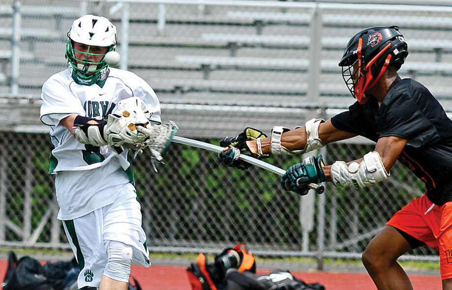 Hour photo / Erik Trautmann Norwalk High School lacrosse battles Stamford High School in their game at Testa Field Saturday