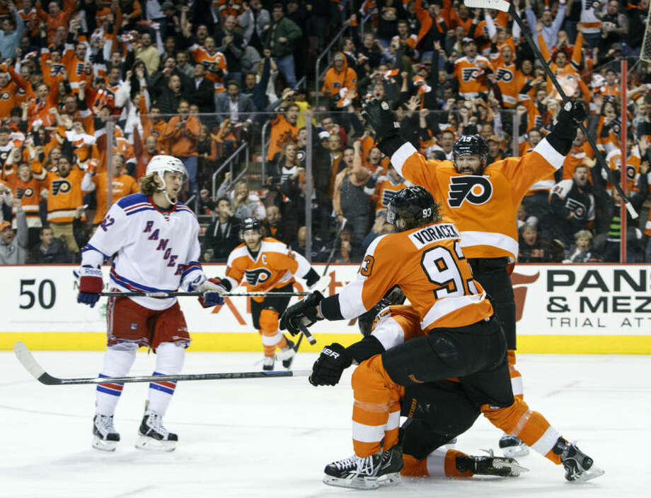 Philadelphia Flyers' Wayne Simmonds, center, celebrates his goal with Jakub Voracek, second from right, of Czech Republic and Scott Hartnell, right, as New York Rangers' Carl Hagelin, left, of Sweden, skates by during the first period in Game 6 of an NHL hockey first-round playoff series, Tuesday, April 29, 2014, in Philadelphia. (AP Photo/Chris Szagola)