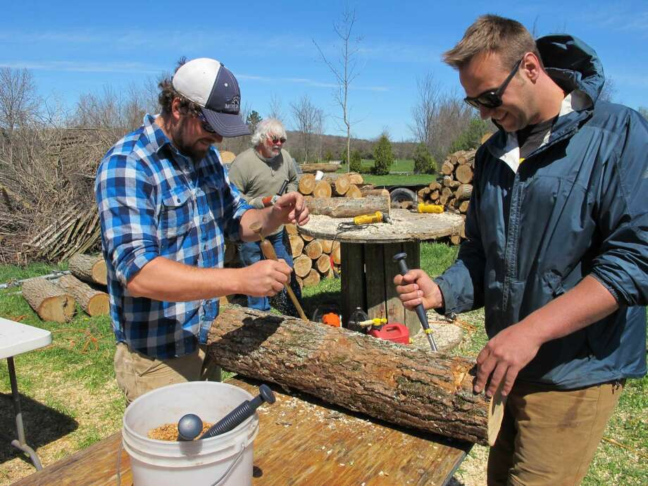 In this Friday, May 6, 2016 photo, mushroom growers Andy Bojanowski, left, and Nick Laskovski inoculate logs with shiitake spawn at Eddy Farm in Middlebury, Vt. The farm will host the sixth annual Shiitakepalooza on Saturday at which volunteers help mushroom growers inoculate logs that will eventually sprout shiitake mushrooms that can bring in $16 to $20 a pound.
