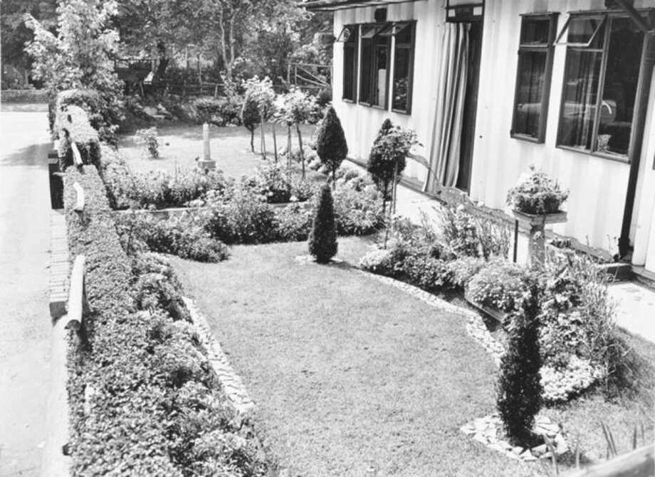 "The smaller footprint of the prefabs allowed for larger gardens; This garden, also in the London district of Streatham, is given structure with stone edging and carefully clipped topiary. Illustrates GARDENING (category l), by Adrian Higgins, (c) 2014, The Washington Post. Moved Thursday, May 01, 2014. (MUST CREDIT: From ""The Gardens of The British Working Class""/London Metropolitan Archives and City of London.)"