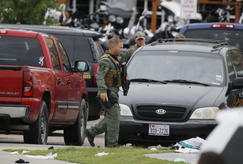 "A law enforcement officer walks past debris near the parking lot of a Twin Peaks restaurant Sunday, May 17, 2015, in Waco, Texas. Waco Police Sgt. W. Patrick Swanton told KWTX-TV there were ""multiple victims"" after gunfire erupted between rival biker gangs at the restaurant. (Rod Aydelotte/Waco Tribune-Herald via AP)"