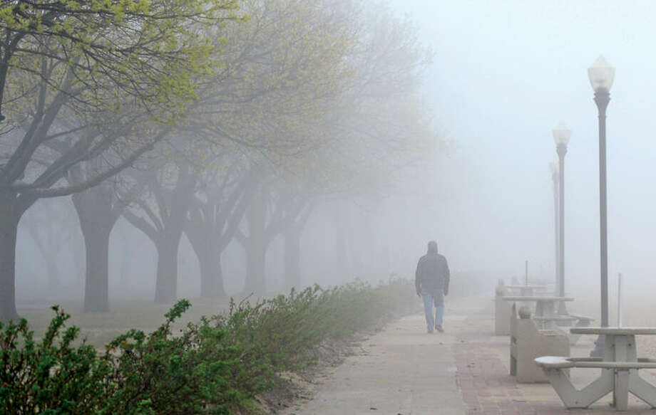 Hour photo / Erik Trautmann A man walks along a foggy Calf Pasture Beach Thursday.