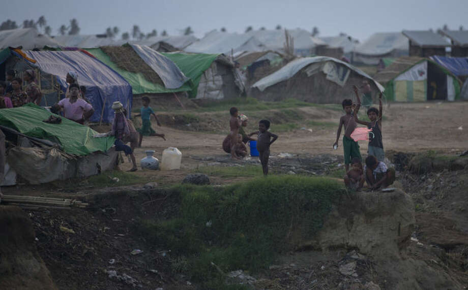 In this May 15, 2013 photo, Rohingya children displaced following 2012 sectarian violence play with a kite on the outskirts of Sittwe, western Rakhine State, Myanmar. Many of those displaced by recent violence live under apartheid-like conditions in tattered canvas tents, and long bamboo houses shared by dozens of families.(AP Photo/Gemunu Amarasinghe)