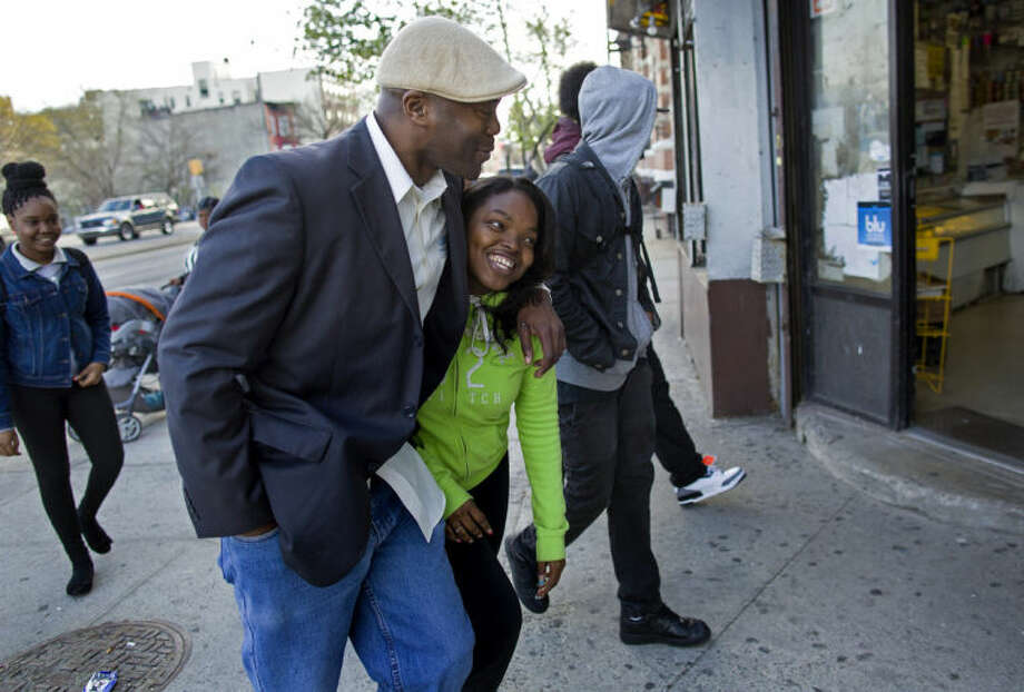 "In a photograph taken Wednesday, April 23, 2014, Dr. Kai Smith, former gang member and now founder and Executive Director of GRAAFICS (Gang Diversion, reentry and Absent Father Intervention Center) jokes with student Tyasia Blair, 16, of East New York, as they walk with other GRAAFICS students in the Brownsville neighborhood of Brooklyn, N.Y. They along with other students at the nearby Brooklyn Collegiate High School enter the GRAAFICS program if they have been part of a ""crew,"" and work to stay focused on getting on with their educations and lives without being part of a neighborhood crew. (AP Photo/Craig Ruttle)"