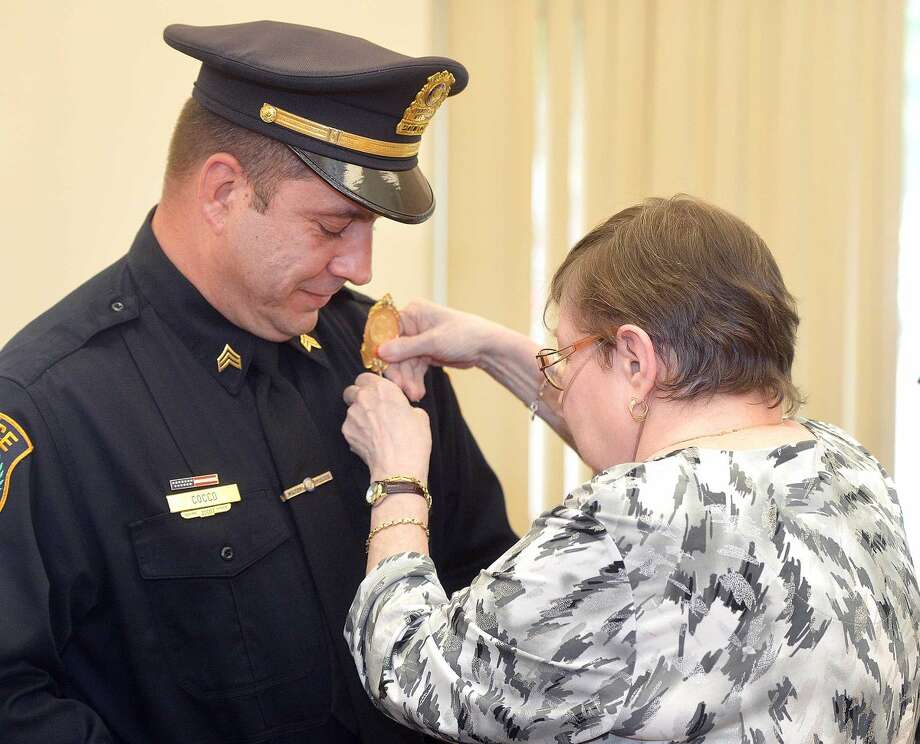 Hour Photo/Alex von Kleydorff Anthony Cocco has his mother Madelyn pin his new badge on after being promoted to Sergeant during a ceremony at Wilton Town hall