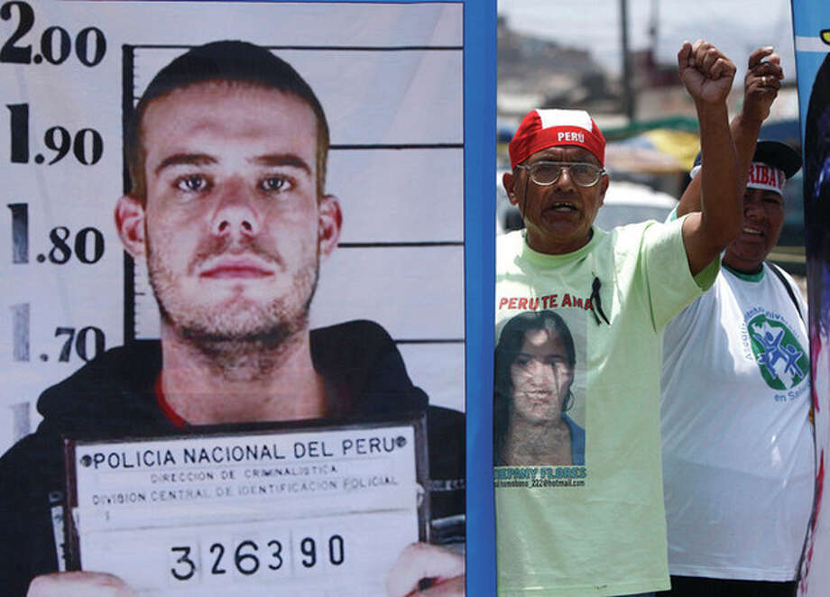 AP photo / Karel Navarro People protest against Joran van der Sloot as they hold up an enlarged picture of his police mug shot outside San Pedro prison where his murder trial is held in Lima, Peru, Wednesday. / 2012 AP