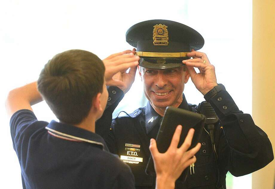 Hour Photo/Alex von Kleydorff Wilton Police Sergeant Arnault Baker has his son Collin help with setting the new gold band on his hat to show that he is now a Sergeant during a promotion ceremony at Wilton Town Hall