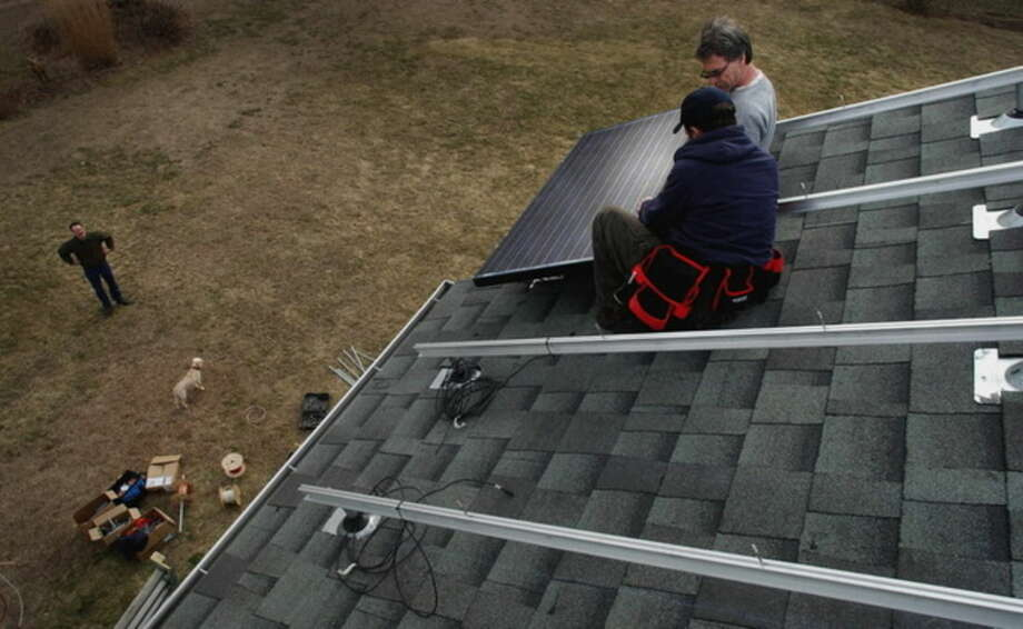 In this March 31, 2005 photo, Paul Israel, President of Sunlight Solar Energy, Inc. of Milford, center, and Duane Andrews, an installer, right, place the first of 24 solar panels of a solar voltaic system on the roof the Dubiel home in Avon, Conn., as Rick Dubiel, the homeowner, left, observes from the ground. Businesses seeking state legislation to streamline local permitting of rooftop solar panels have run into opposition from municipal officials who say proposed rules are a costly mandate. (Stephen Dunn/The Hartford Courant via AP)