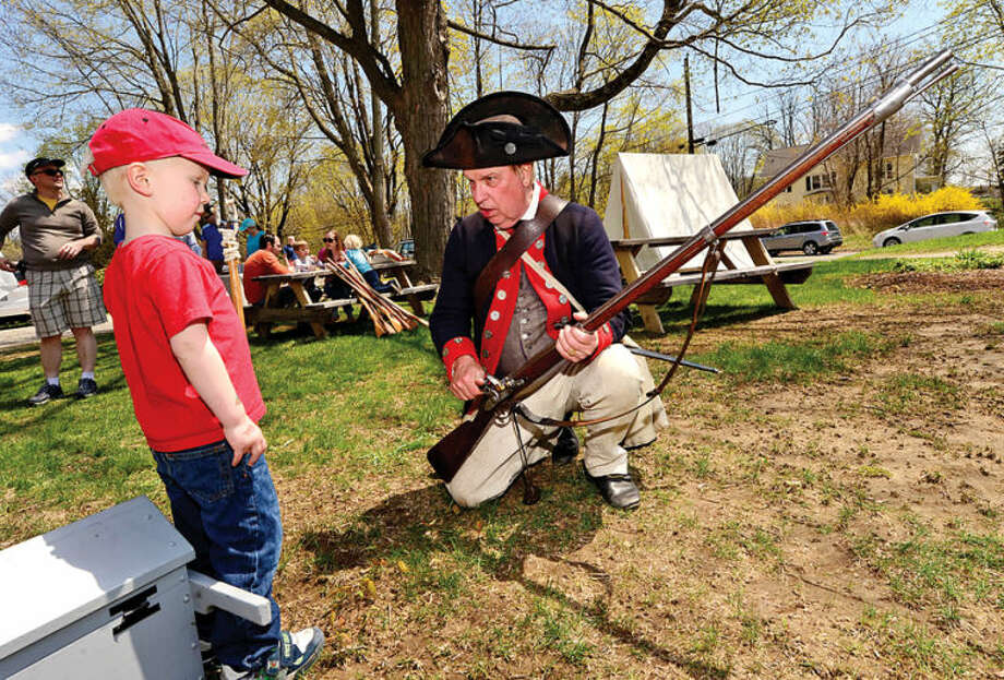 5 year old Max Fleming learns about muskets from reenactor Roger Smith during the Wilton Historical Society Barn Raising Day Saturday in Wilton.