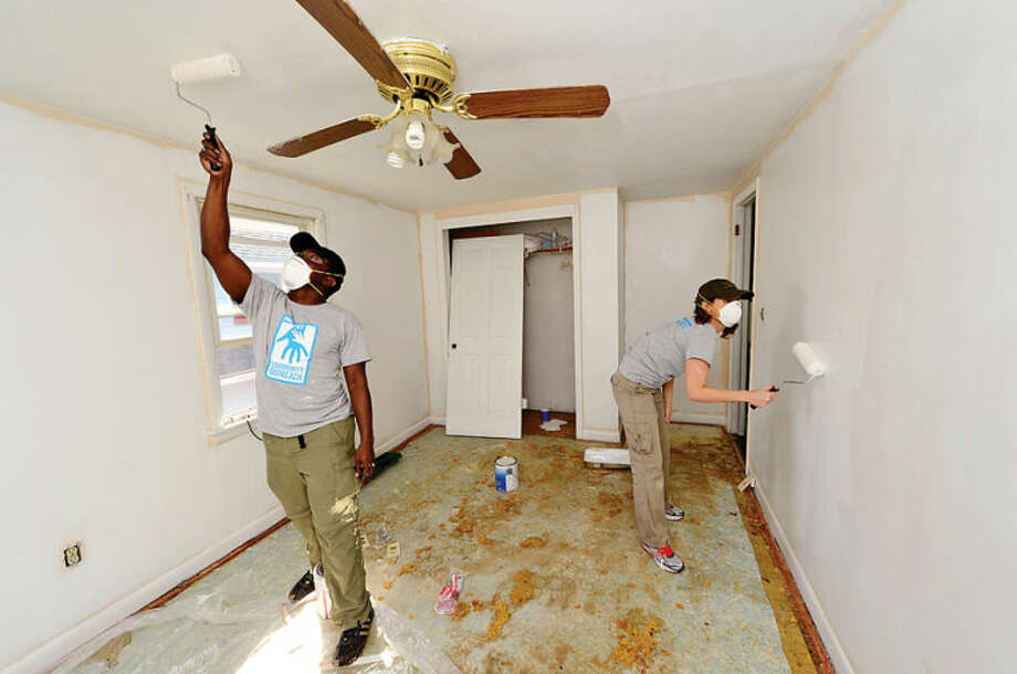 Hour photo / Erik Trautmann Facset Volunteers Banji Iyun and Kathleen Fischer paint the interior of a house at 9 Moore Place in Norwalk for HomeFront Day Saturday.