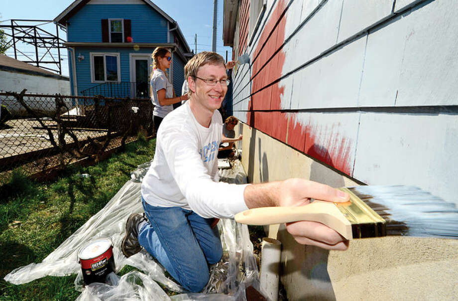 Hour photo / Erik Trautmann Facset Volunteers including Ed Jorkerpaint the exetrior of a house at 9 Moore Place in Norwalk for HomeFront Day Saturday.