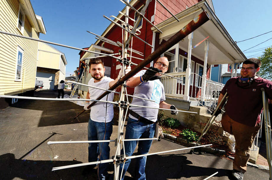 Hour photo / Erik Trautmann Facset Volunteers Jonathan Rodriguez and Alan Davis repair a house at 9 Moore Place in Norwalk for HomeFront Day Saturday.