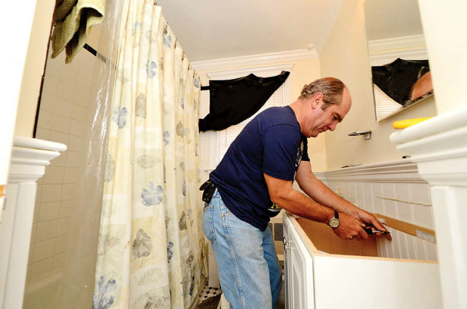 Hour photo / Erik Trautmann This Old House volunteer Richard Thethewey replaces a vanity at a home on Walter Ave in Norwalk for HomeFront Day Saturday.