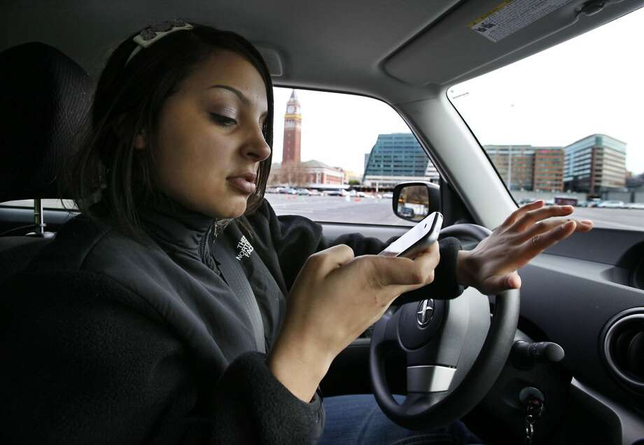 New driver Brandi Eadie, 16, looks down at her cell phone to read a text message as she drives through a rubber-cone course in Seattle on Wednesday, Jan. 6, 2010 to demonstrate the dangers of phone use while driving. Eadie, who volunteered for the Driven to Distraction Task Force of Washington State event because she thought she could show organizers that she could safely drive and text at the same time, knocked down multiple cones meant to simulate where pedestrians or other objects could be. Sen. Tracey Eide, D-Federal Way, who helped organize the event, is planning to sponsor legislation to make operating a cell phone while driving a primary offense. (AP Photo/Elaine Thompson)
