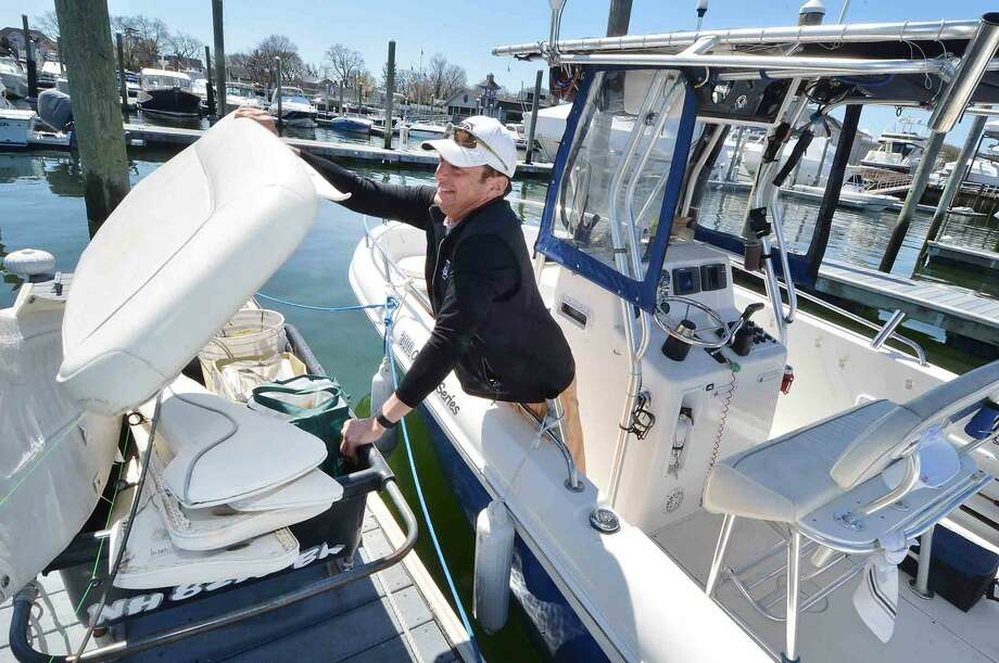 At his dock at Rex Marine, Kevin Greco grabs the seat cushions from the cart for his 24 ft. Center Console boat as he prepares to go fishing on Sunday morning in Norwalk Conn. on April 17